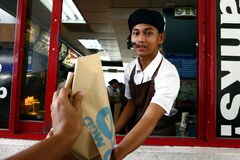 Worker At A Fast Food Restaurant Give The Food Order Of A Customer At A Drive Thru Window Royalty Free Stock Photography