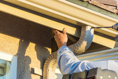 Worker Attaching Aluminum Rain Gutter and Down Spout to Fascia o Royalty Free Stock Images