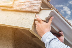 Worker Attaching Aluminum Rain Gutter to Fascia of House. Royalty Free Stock Photography