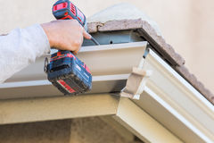 Worker Attaching Aluminum Rain Gutter to Fascia of House. Royalty Free Stock Photo