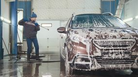 Worker in auto service is washing a car in the suds by water hoses. Telephoto Royalty Free Stock Photo
