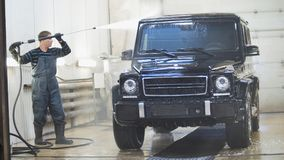 Worker in auto service is washing a luxury car in the suds by water hoses. Telephoto Stock Images