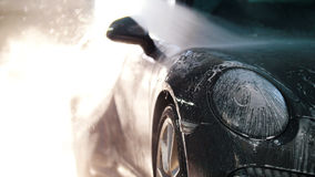 Worker in auto service is washing a luxury car by water hoses, backlight Stock Photo