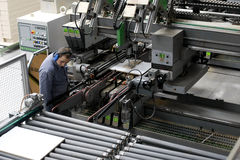 Worker in automatic furniture factory. A worker supervises the automated production process in a large wood furniture factory royalty free stock photo