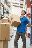 Worker with backache while lifting box in warehouse Stock Images