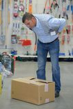Worker with backache while lifting box in warehouse. Worker with backache while lifting box in the warehouse Stock Photography