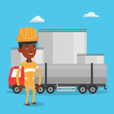 Worker on background of fuel truck and oil plant. African refinery worker of oil and gas industry. Worker standing on the background of fuel truck and oil Royalty Free Stock Photo