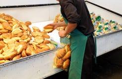 Worker in a bakery packaging bread. Worker in a bakery packaging white bread Royalty Free Stock Photos