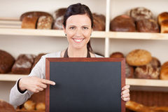 Worker in a bakery pointing to a blank board. Pretty worker in a bakery pointing to a blank chalkboard with a friendly smile with copyspace on the board for your royalty free stock photos