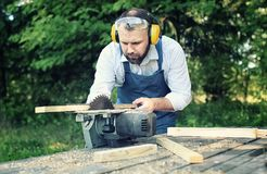 Worker beard man with circular saw. Desktop items, and the process of preparation of wood for sawing and construction Royalty Free Stock Photography