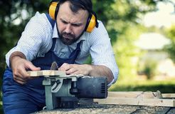 Worker beard man with circular saw. Desktop items, and the process of preparation of wood for sawing and construction Stock Photography