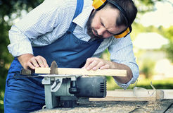 Worker beard man with circular saw. Desktop items, and the process of preparation of wood for sawing and construction Royalty Free Stock Image