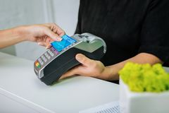 Worker of beauty salon holding pin pad while client paying by card royalty free stock image