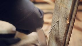 Disposal of old boards. Worker bends nails in old boards. Disposal of old boards. The hammer hits the nail and bends it. Close up