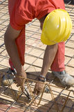 Worker Bends to  Cut Wire - Vertical Royalty Free Stock Photo
