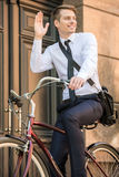Worker with bicycle. Image of a young young handsome businessman riding bicycle Stock Image