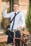 Worker with bicycle. Portrait of young businessman riding bicycle to work on urban street Royalty Free Stock Photo