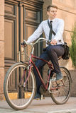 Worker with bicycle. Portrait of young businessman riding bicycle to work on urban street Royalty Free Stock Photos
