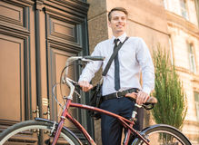 Worker with bicycle. Young handsome office worker going to work on his bicycle. Healthy lifestyle concept Royalty Free Stock Image