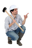 Worker with big hammer. Laborer kneeling with a sledge hammer Stock Photos