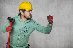 A worker with a big hammer, ready for the challenge. Protective helmet on the head Stock Photography