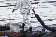A Worker in biohazard suits used Oil Containment boom as cleani. Ng crude oil from the beach royalty free stock image