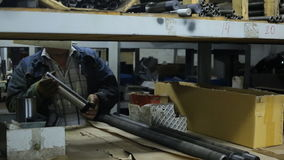 Worker in a blue denim jacket takes off shelf metal detail part to work. stock video footage