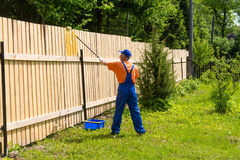 Worker in blue overalls, orange t-shirt, cap and gloves painting a wooden fence Stock Photo
