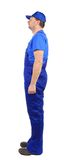 Worker in blue overalls. Side view. Stock Images