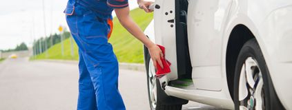 Worker in blue pants, wipes the car door with a red rag royalty free stock photography