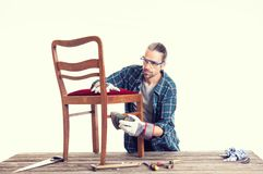 Worker in blue shirt repair old chair stock images