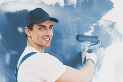 Worker in Blue Romper Paints with Paint Roller. Worker in Blue Romper Paints Wall with Paint Roller. Repair in Apartment. Modern Construction and Engineering Royalty Free Stock Image