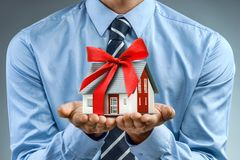 Worker in blue shirt holding house with red ribbon Royalty Free Stock Photos