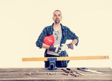 Worker in blue shirt sawing wood stock images