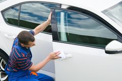 Worker in a blue suit, wipes the car with a white rag royalty free stock photography