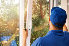 Worker installing new plastic pvc window. Worker in blue uniform installing new plastic pvc window royalty free stock photo