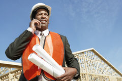 Worker With Blueprints Using Cell Phone At Construction Site Royalty Free Stock Photography