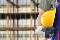 Worker with blurred construction in background Royalty Free Stock Photo