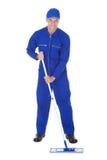 Worker In Boilersuit Cleaning Floor Royalty Free Stock Image