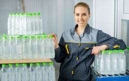 Worker with bottled water. Female worker with packed water bottles at a factory Royalty Free Stock Photo