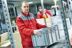 Worker with box at warehouse conveyer. Worker men with box near conveyer at automobile spare part warehouse stock photos