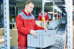 Worker with box at warehouse conveyer. Worker men with box near conveyer at automobile spare part warehouse stock images