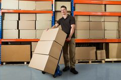 Worker With Boxes On Hand Truck In Warehouse. Happy Male Worker With Boxes On Hand Truck In Large Warehouse Royalty Free Stock Photo