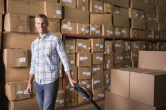 Worker with boxes in warehouse. Portrait of worker standing with boxes in warehouse royalty free stock photos