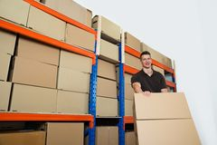 Worker With Boxes In Warehouse. Young Happy Male Worker With Boxes In Warehouse Royalty Free Stock Photos