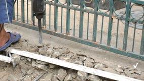 Worker breaking cement floor by using demolition hammer stock video footage