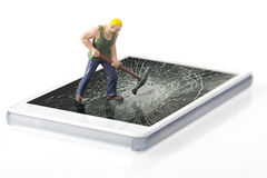 Worker breaking smart phone. Miniature worker breaking glass of smart phone royalty free stock photos