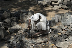 Worker breaking stones. Mumbai, India. Worker breaking stones in the street of Mumbai. Sculptor turbaned hammer stock image
