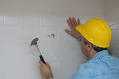 Worker breaking up a bathroom wall Stock Images