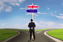 Worker with brexit signpost. Brexit concept. Male worker standing on the road with flag of UK and EU on the signpost royalty free stock photo